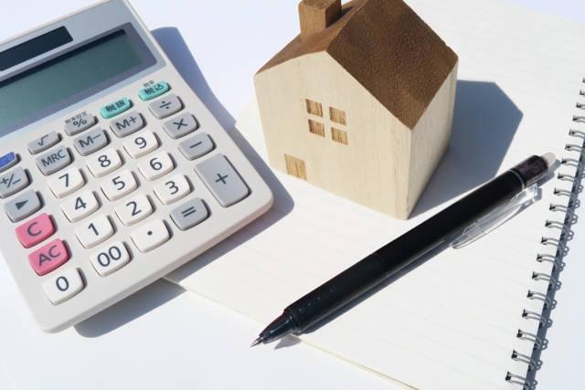 家の置物と電卓とペン
