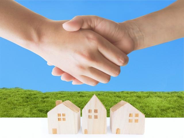 青空と家のオブジェと握手する手