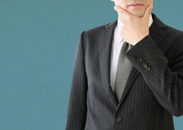 考えるスーツの男性