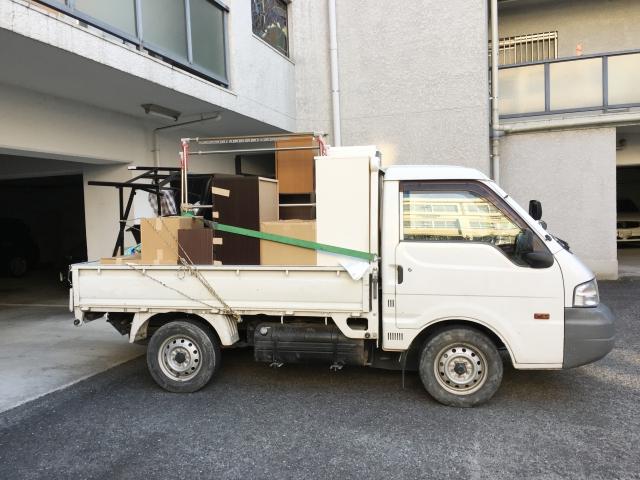 不用品を荷台に積んだ軽トラック