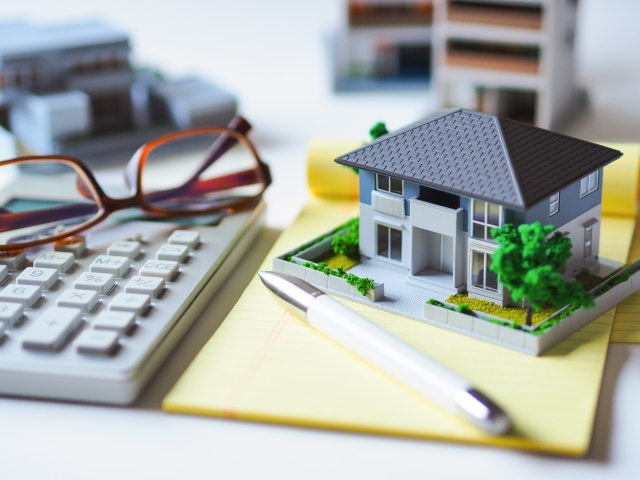 家の模型と電卓とノート