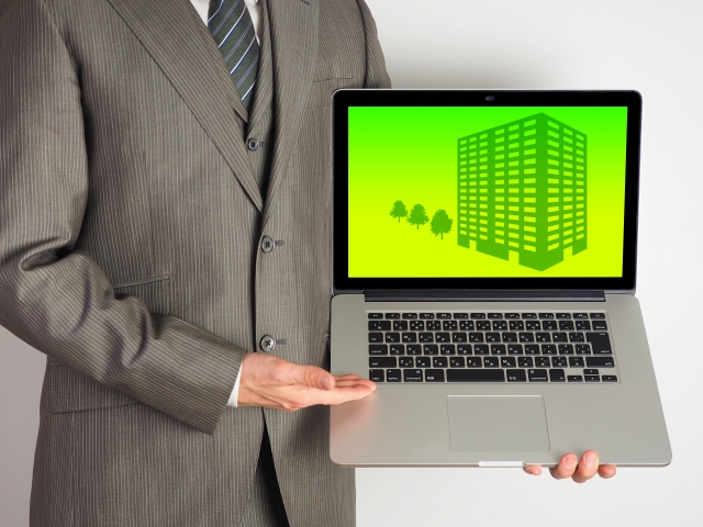 pcでマンションについて説明する営業マン