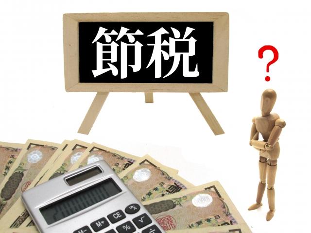 節税について悩む人形とお金と電卓