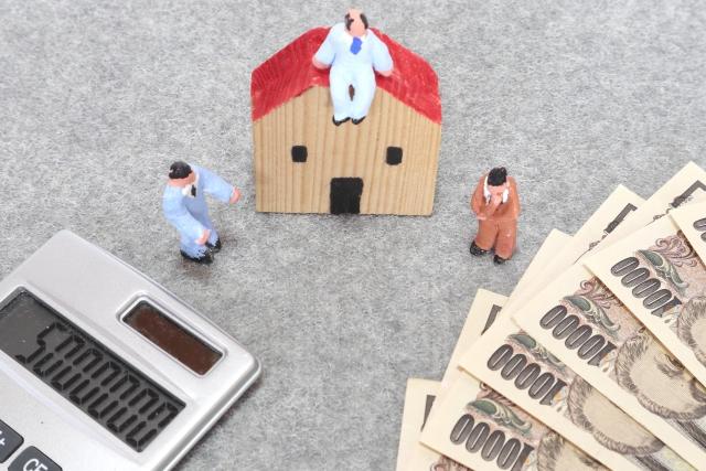 家の模型と電卓と紙幣