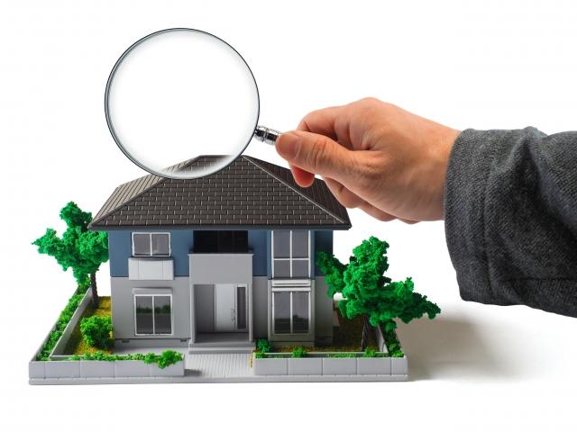 家の模型と虫眼鏡のイメージ