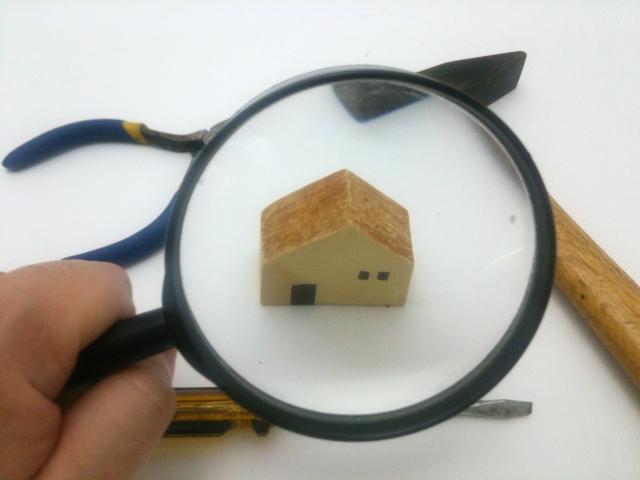 ルーペで覗かれた積み木の家と工具
