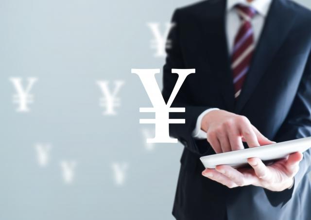 電卓で計算をするビジネスマン