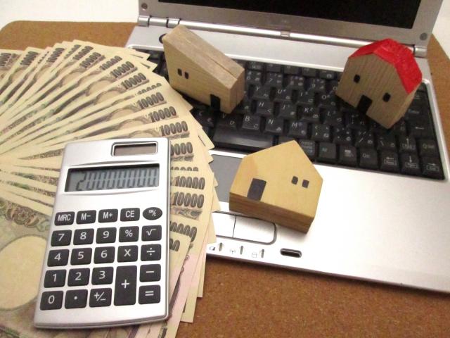 お金と電卓と家の積み木