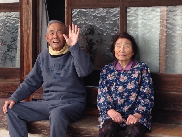 縁側に座って手を振るシニア夫婦