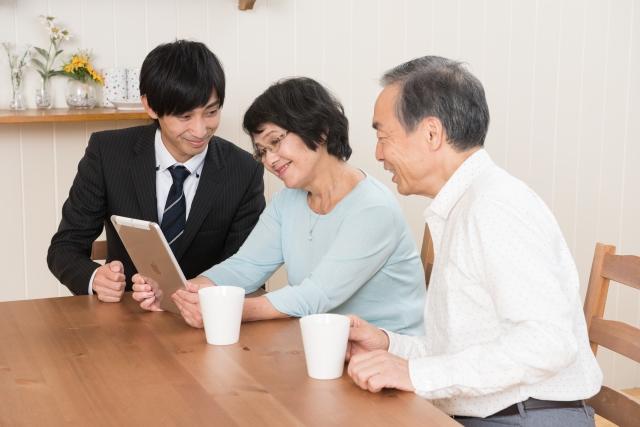 タブレットを見ながら営業マンから説明を受けるシニア夫婦