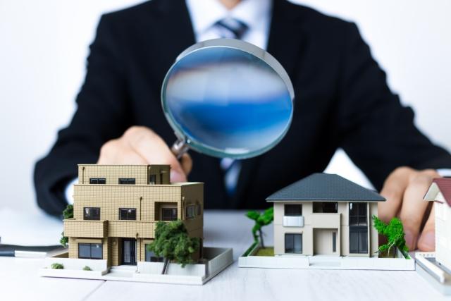 ミニチュアの家を虫眼鏡で調べるビジネスマン