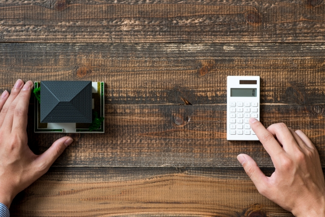 ミニチュアの家と電卓で計算する手