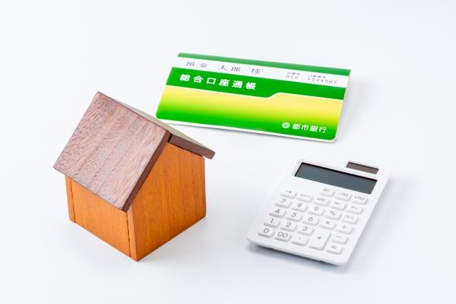ミニチュアの家と電卓と通帳